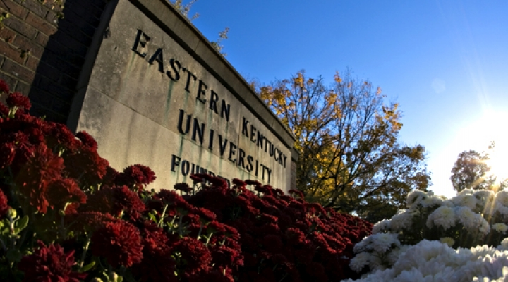 EKU stone sign with maroon and white flowers